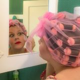 Woman with hair in rollers looking in mirror and applying makeup