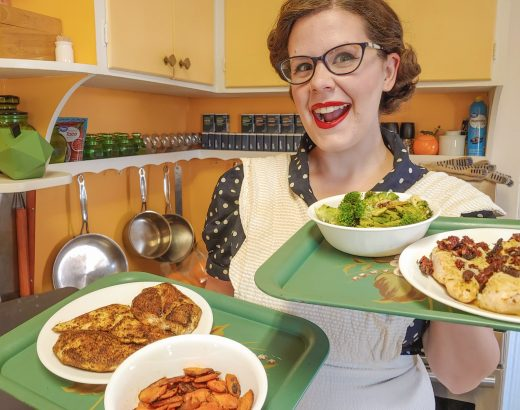 Vintage housewife holding two separate easy chicken dinners