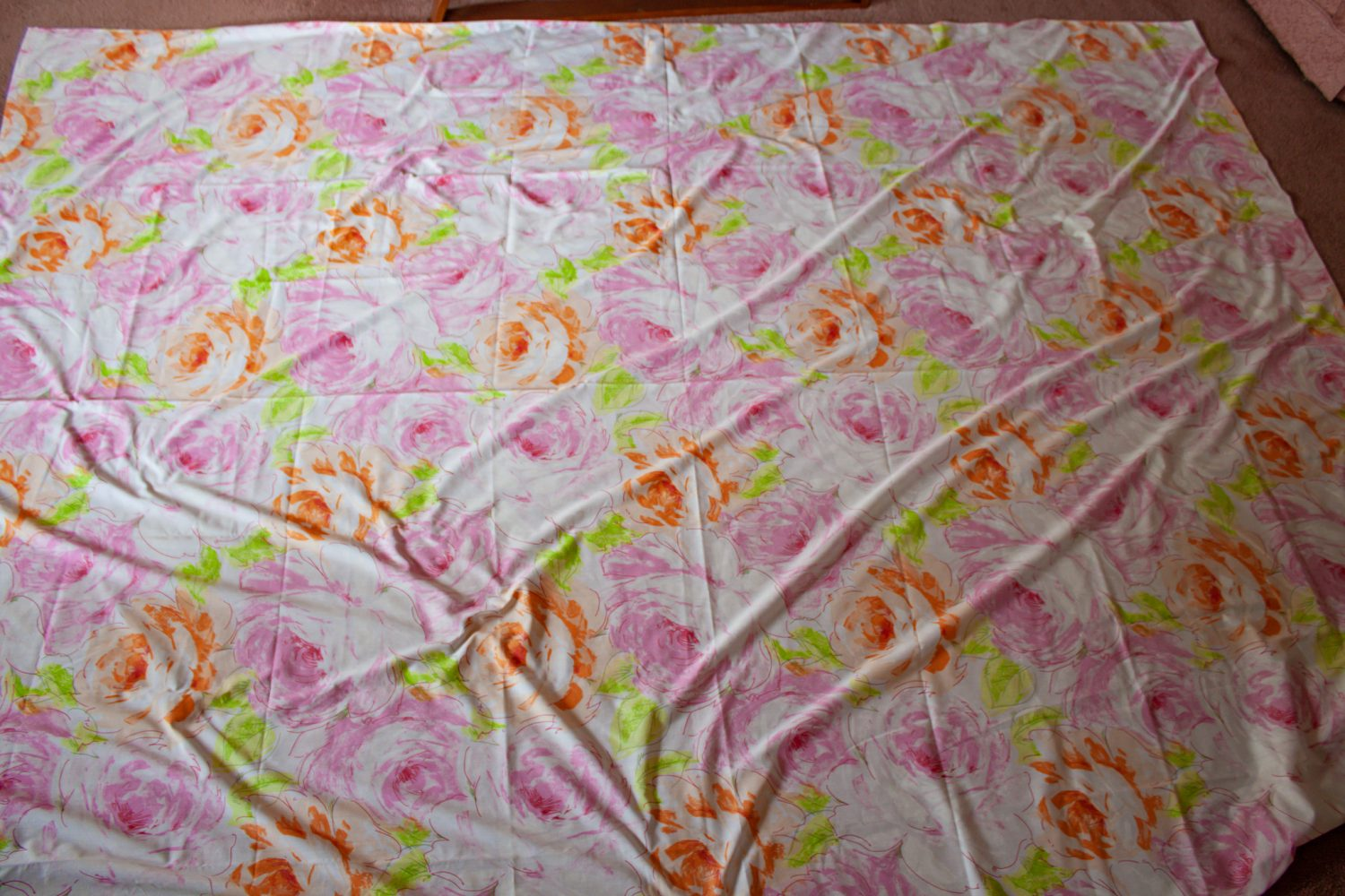Flat floral patterned sheet laid out on the floor