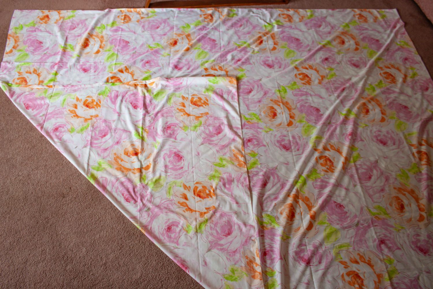 Fabric laid out on floor with one corner folded up to form a triangle