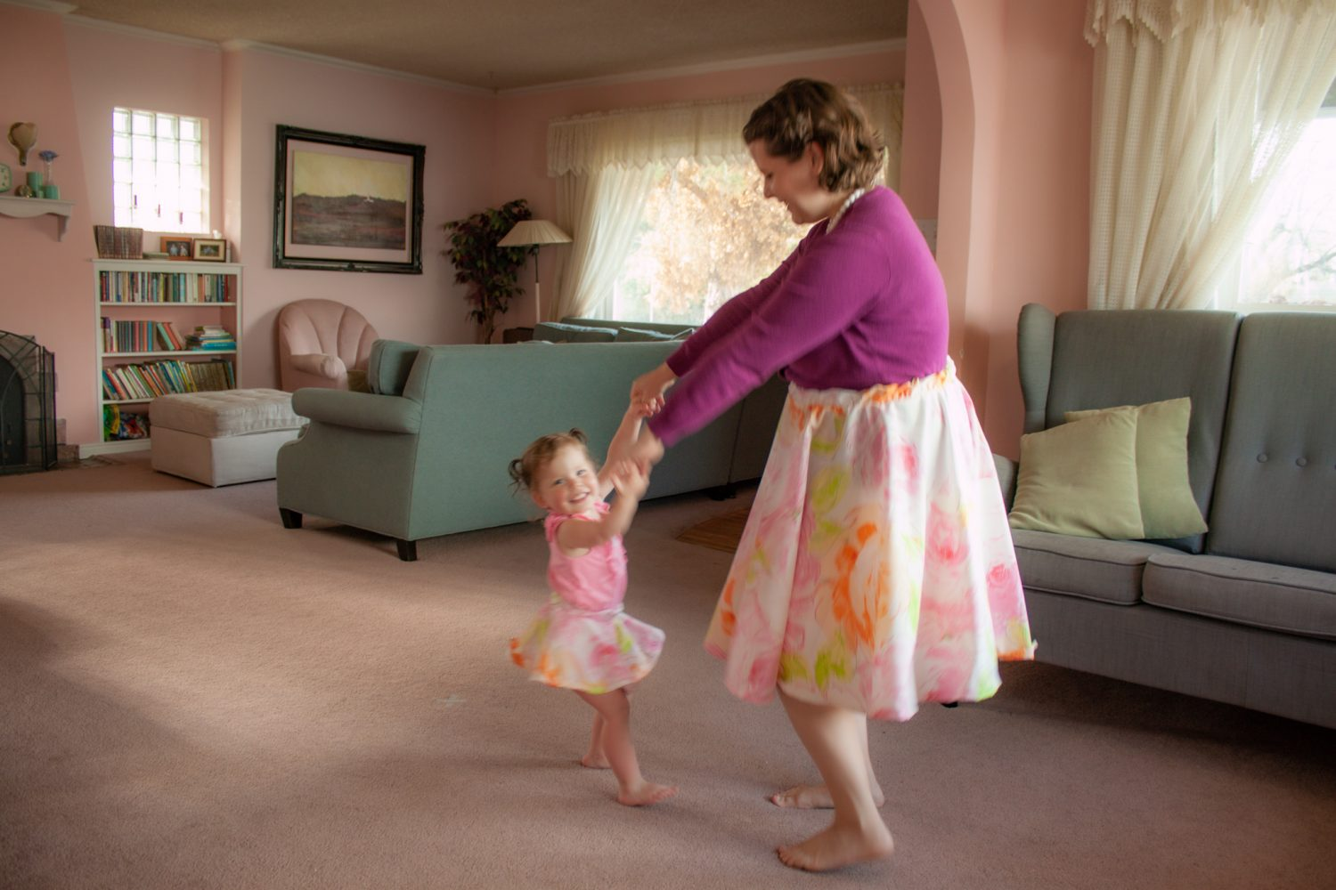 Mother and toddler girl dancing in matching circle skirts