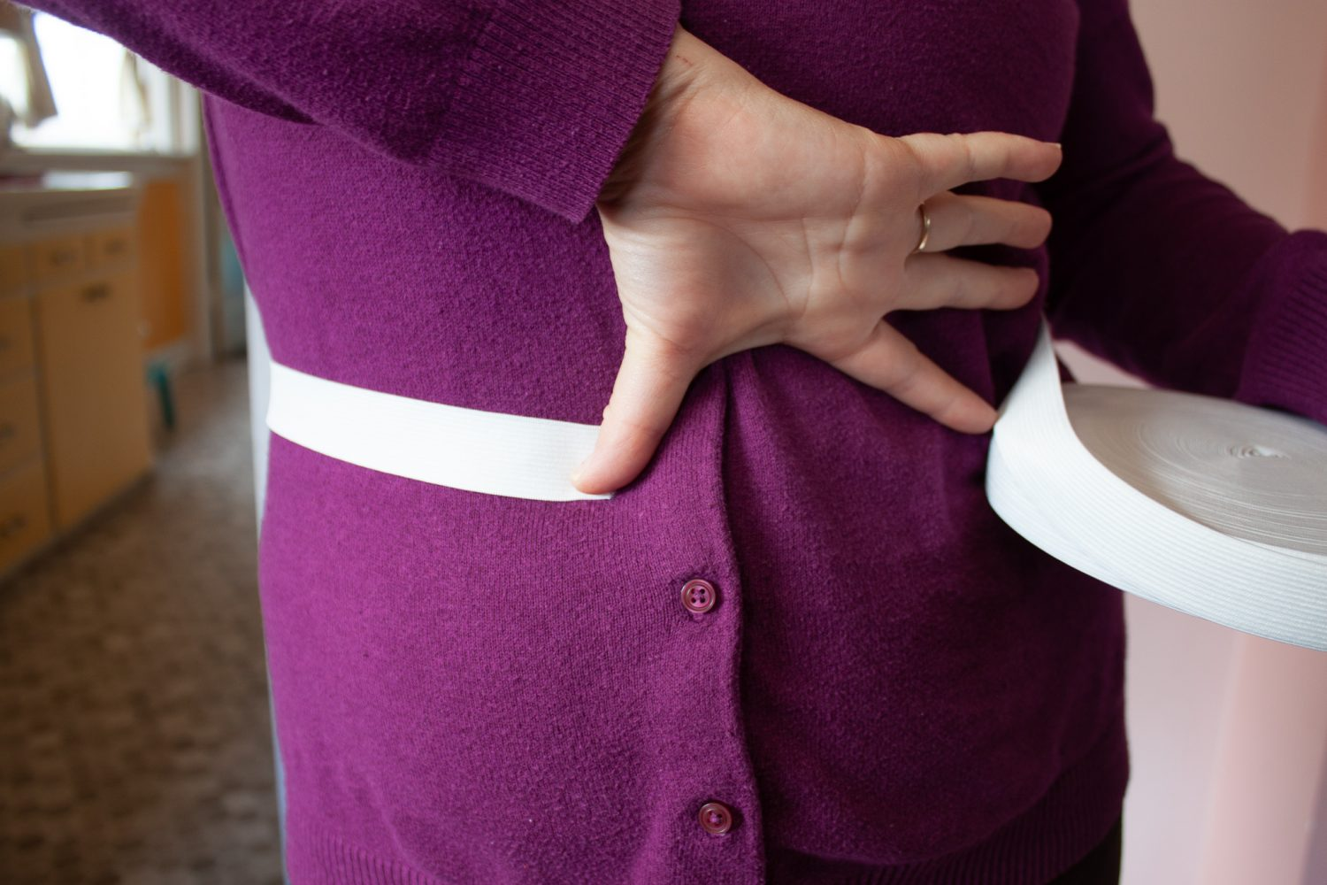 Elastic wrapped around waist with outstretched hand measuring gap
