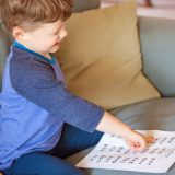 Young boy reading from a nonsense word worksheet