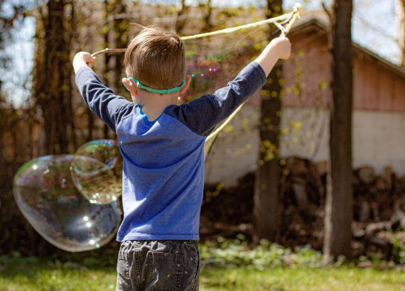 Young boy with tri-string bubble wand and two giant bubbles