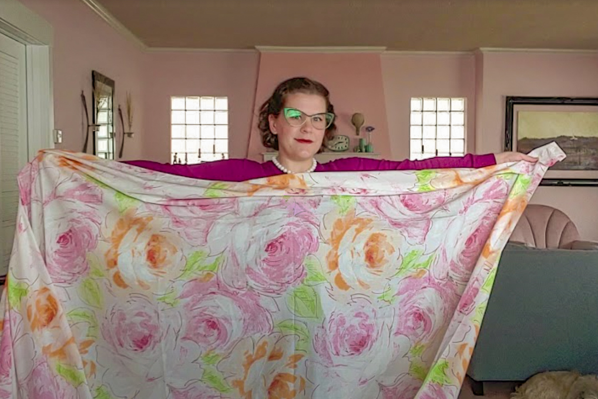 Kelli holding up floral sheet between outstretched arms